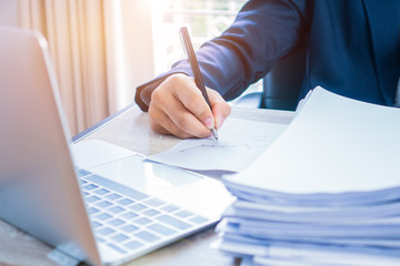 Businessman hands working and writing data in computer, Stacks of paper files for searching information on work office, business report papers,piles of unfinished documents achieves with clips indoor