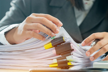Accounting planning budget concept : Business woman offices working for arranging documents unfinished stack of document papers with pen, calculator, clip papers on busy office desk Wall mural