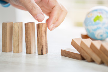 Strategy planning risk in business concept : Businessman or engineer placing wooden block dominos on table with blur global model. Alternative risk for goal and success