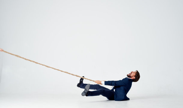 business man pulls the rope on an isolated white background