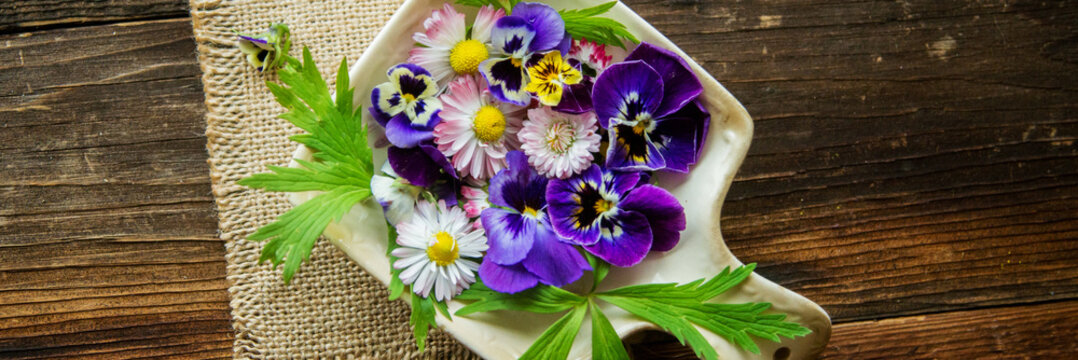 Fresh salad with smoked salmon, black olives, cherry tomatoes and edible flowers on wooden background.