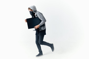 robbery man thief in the hood stole a laptop runs