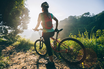 Young woman cyclist carrying mountain bike on summer forest trail Wall mural