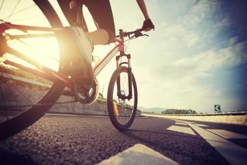 Woman cyclist legs riding Mountain Bike on highway