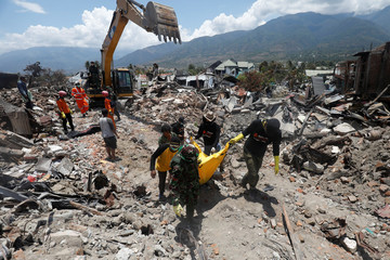A victim of last week's earthquake is recovered in the Balaroa neighbourhood in Palu, Central Sulawesi