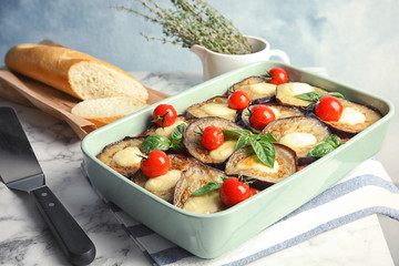 Baked eggplant with tomatoes, cheese and basil in dishware on marble table