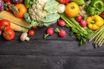 Flat lay composition with assortment of fresh vegetables on wooden table. Space for text