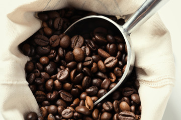 Bag with scoop and roasted coffee beans, closeup