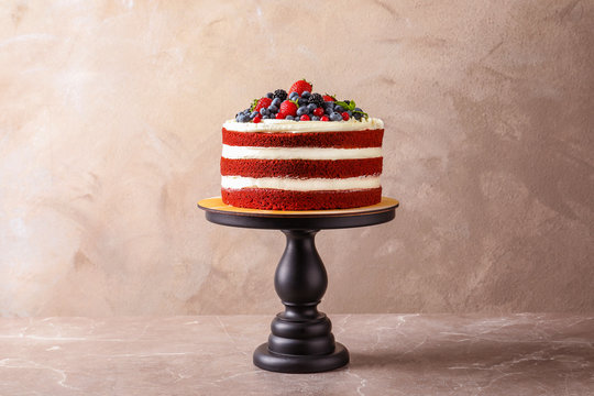 Stand with delicious homemade red velvet cake on color background