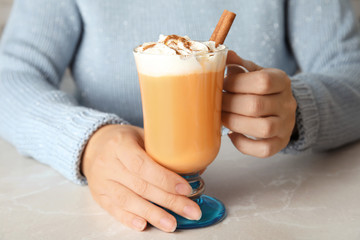 Woman holding glass cup with pumpkin spice latte and whipped cream on light table