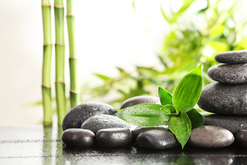 Bamboo leaves with spa stones on table against blurred background. Space for text