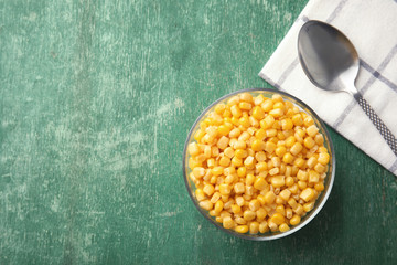 Bowl with corn kernels on green wooden background, top view. Space for text