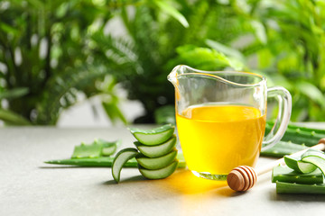 Fresh aloe vera leaves and jug of honey on table against blurred background with space for text