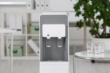 Modern water cooler and table with glasses in office