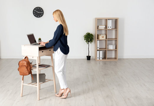Young woman using laptop at stand up workplace indoors