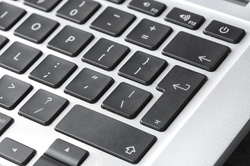 Modern laptop keyboard with black buttons, closeup view