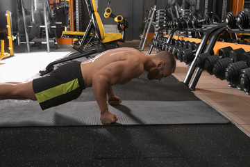 Strong man doing plank exercise in gym