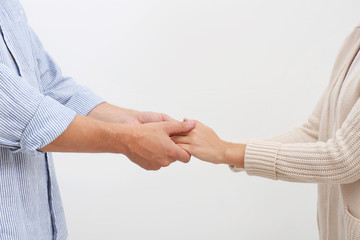 Man holding woman's hands on light background. Concept of support and help