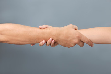 People holding hands together on gray background, closeup. Concept of support and help