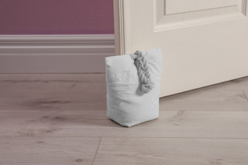 Stuffed bag holding wooden door at home