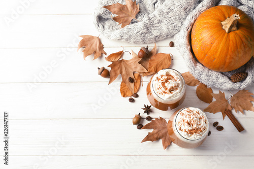 Flat lay composition with glasses of tasty pumpkin spice latte and space for text on wooden background