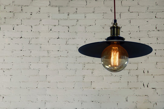 Industrial Style Light Pendant with Decorative Edison Filament Bulb on White Brick Wall Background