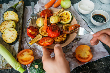 Healthy and healthy food: grilled vegetables and men's hand with fork in the frame, zucchini, eggplant, tomato, onion cooked on fire, on a dark background