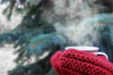 Female hands in red knitted mittens holding steaming cup of hot coffee or tea near fir christmas tree. Winter time concept.