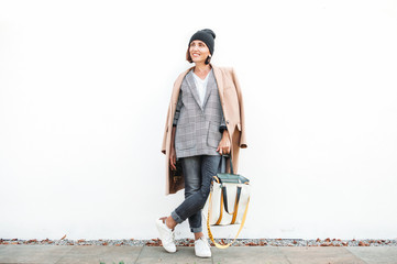 Wall Mural - City street fashion look. Woman dressed in multilayered outfit for autumn days