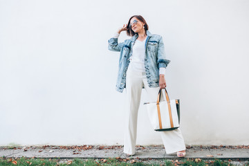 Wall Mural - Woman posing in elegant outfit with oversize denim jacket and shopper bag