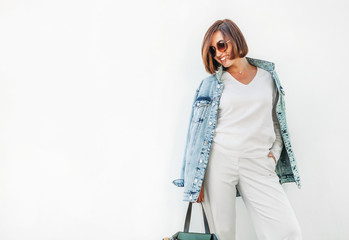 Wall Mural - Posing woman in elegant white outfit with oversize denim jacket