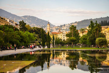 Old clock tower in the city of Nice, French Riviera. Reflections in the water of the Promenade du Paillon park.
