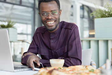Glad smiling dark skinned male entrepreneur reads sms message with good notification on smart phone, watches video blog, works on laptop computer, wears round optical glasses, formal clothes