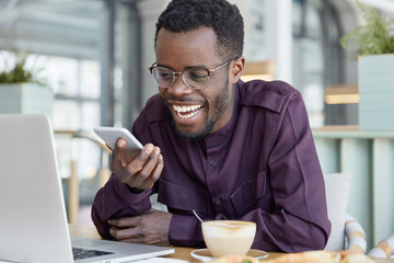 Dark skinned graphic designer sends text message, glad to recieve good notification, sits at desktop, drinks hot coffee, dressed in purple shirt. Handsome black man plans his freelance schedule