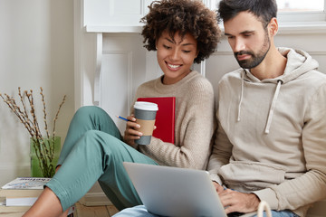 Photo of happy multiracial male and female friends watch video on laptop computer, have leisure time at home. Classmates enjoy common online project, sit closely, carry disposable cup of cappuccino