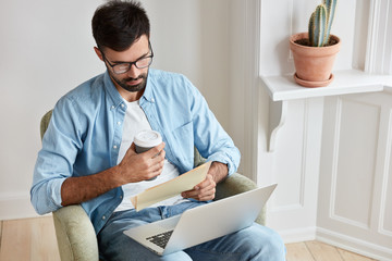 Serious entrepreneur takes care of business, works at home, concentrated into documents, has laptop computer on knees, holds takeaway coffee, sits in comfortable armchair. People and work concept