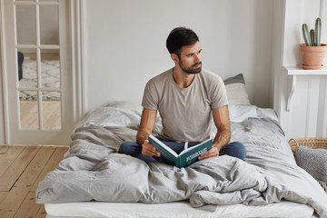 Horizontal view of thoughtful bearded man holds book, studies business issues, prepares for financial report, dressed in casual clothes, sits crossed legs on comfortable bed in modern apartment