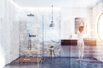 Woman in white tile and crude wall bathroom