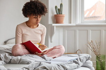 Beautiful African American woman sits on bed, crosses legs, makes some notes at diary holds pen in hands, dressed in pyjamas. Rest, comfort and people concept. Female writes dreams and goals