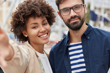 Outdoor shot of lovely mixed race couple have stroll together, stand next to each other, pose for making selfie, being in good mood. Diverse friends take picture of themselves. Tourists go sightseeing