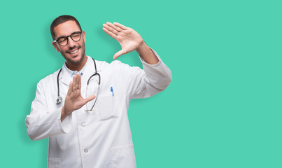 Happy young doctor doing a frame gesture with his hands