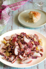 Octopus salad and potatoes, in a rustic wooden background. Mediterranean food