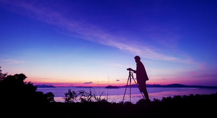 Silhouette young photography man take a photo in sunrise or sunset beautiful scenery.