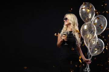 Obraz Brightfull expressions of happy emotions of  amazing blonde girl celebrating party on black background. Luxury black dresses, smiling, a glass of champagne, golden tinsels,  balloons, long curly hair - fototapety do salonu
