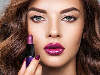 Young beautiful girl holds purple lipstick close to face