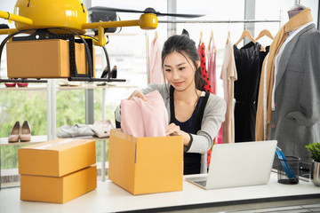 Young asian women packing cloth on box for delivery to customer by air drone, Small business with modern technology shipment innovation and eco concept