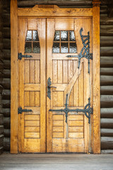 Outdoor front view of a naturally wood finished door entrence. Rustic traditional decorative pattern with iron fittings.