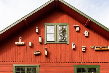 Outdoor front view of many bird nest boxes on red exterior wooden building wall with windows.