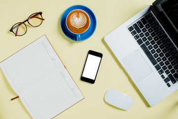 Yellow minimal desk with laptop,mouse,glasses,notebook,smart phone and cup of coffee.Top view with copy space.