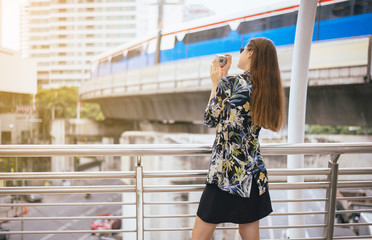 Woman tourist walking in the center of Bangkok and taking photo with digital camera
